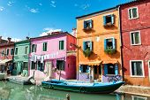 Colorful houses with drying laundry hanging on the facades, Burano, Venice, Italy, painted in bright