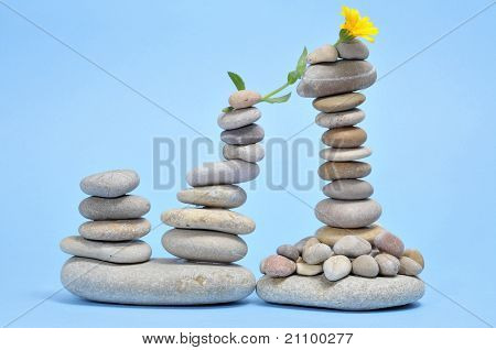 some piles of zen stones and yellow daisy on a blue background