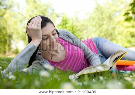 Woman Listening Music And Reading Book In Park