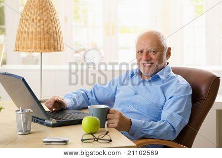 Portrait of happy senior man sitting at desk using laptop computer at home, smiling at camera.