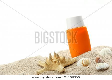 Bottle of sunblock with shells on sand