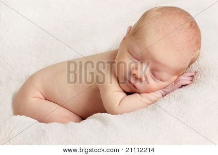 Newborn sleeping baby boy on a white blanket.