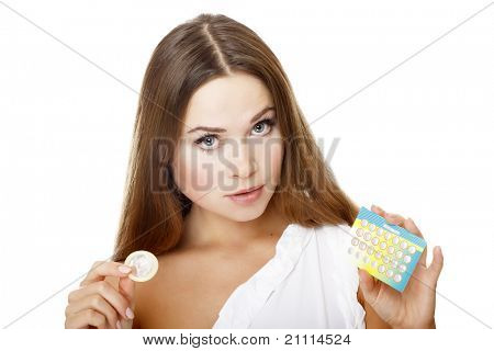 Pretty girl with condom and contraceptive pills. Isolated over a white background.