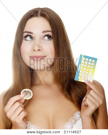 Pretty girl with condom and contraceptive pills. Isolated over a white background