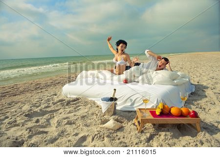 Beautiful young couple yawning in bed in morning on the beach