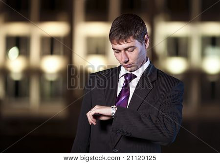 Handsome businessman watching time at night city in the background