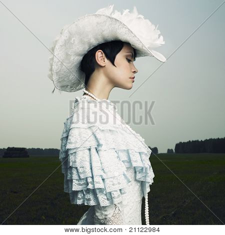 Beautiful woman in vintage cap on nature
