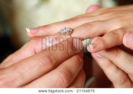 Closeup of hands of a bride and a groom, a man putting a ring on his woman's finger