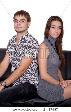 Funny Nerd Guy And Glamorous Girl Sitting On The Sofa Isolated On White