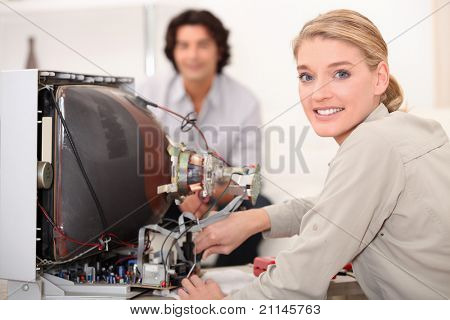 Woman repairing television set