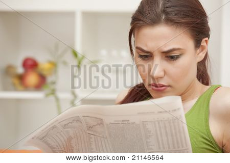 Woman Reading Bad News In Newspaper