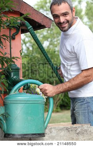a mid aged man filling a  watering can with a cast iron water pump