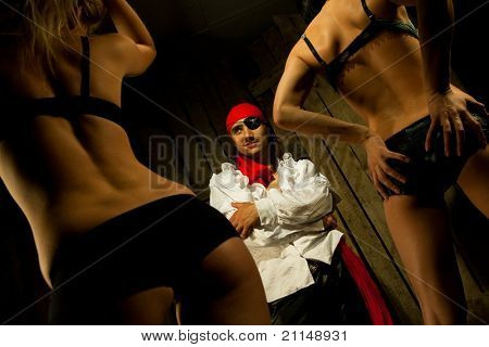 Pirate  with pair Sexy passionate girls against wooden background
