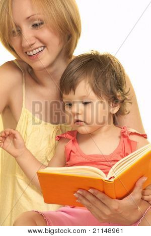 Young mother with her daughter reading book at home