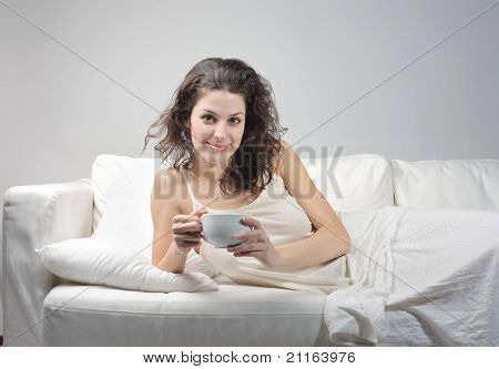 Beautiful woman lying on a sofa and holding a cup of tea