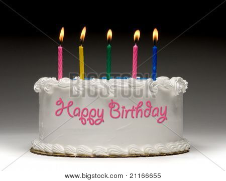 """White birthday cake profile on gradient background with five colorful lit candles and """"Happy Birthday"""" written on the side with frosting"""