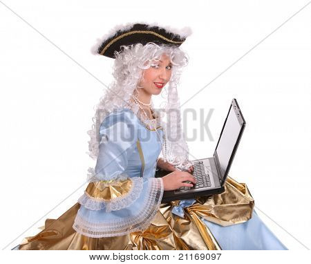 Woman in ancient dress of marquise with laptop.