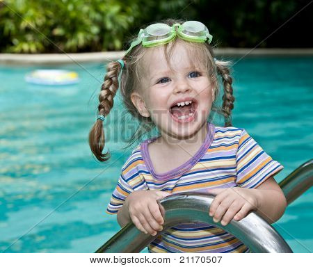 Baby in protective goggles leaves pool.