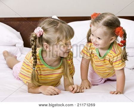 Happy family on white bed.  Two children.