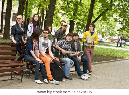 Group of people on bench in park. Outdoor.