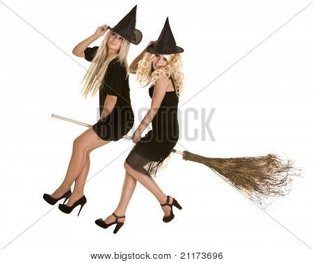 Two Halloween witch blond in black dress and hat fly on broom.Isolated.