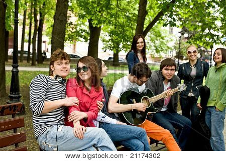 Group of people in city park listen music.Outdoor.