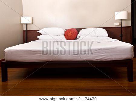 Bett und Kopfteil in Schlafzimmer mit Lampe. Innenraum.