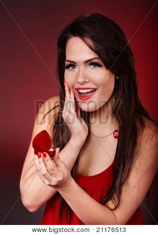 Girl with jewellery gift box on red background. Valentines day.