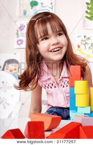 Child with wood  block and construction set in play room.  Preschool.