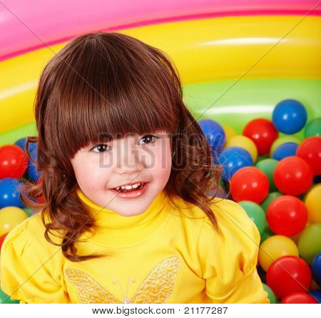 Little girl with group ball. Play room.