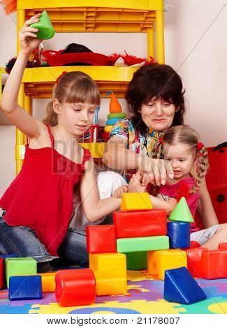 Children  with  block and senior woman in play room.  Preschool.