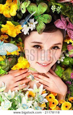Linda menina com borboleta e flores na grama verde. Ao ar livre.