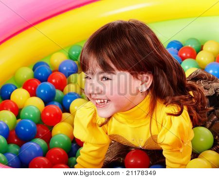 Happy little girl in group colorful ball.