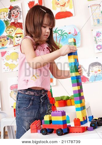 Child with construction set in play room. Preschool.