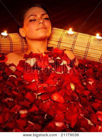Hermosa chica en el jacuzzi con pétalos de rosa y velas. Cuidado del cuerpo.
