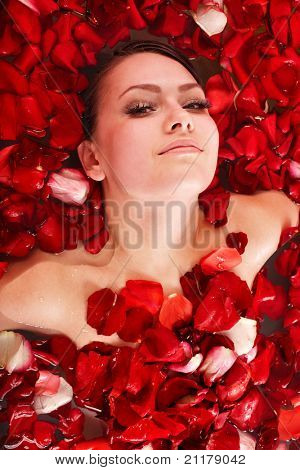 Beautiful girl in jacuzzi with rose petal. Body care.