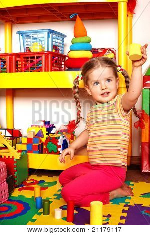 Child with puzzle and wood block  in play room.  Preschool.