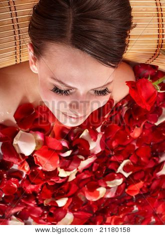Young woman in jacuzzi with rose petal.