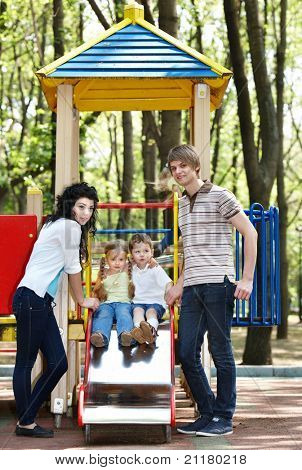 Outdoor happy family with too children on slide.