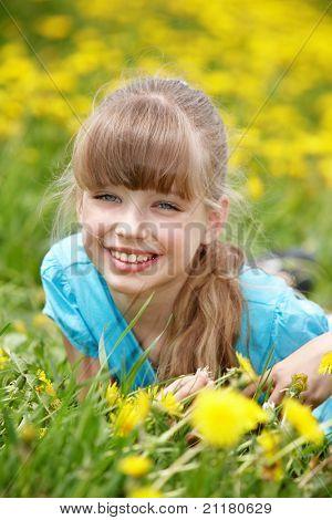 Little girl lying on grass in flower. Outdoor.