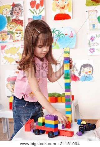 Little girl playing construction set in play room.