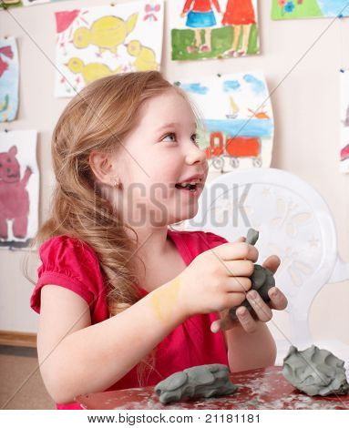 Little girl moulding from clay in play room.