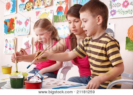 Pintura con el profesor en clase de arte a los niños. Cuidado de niños.