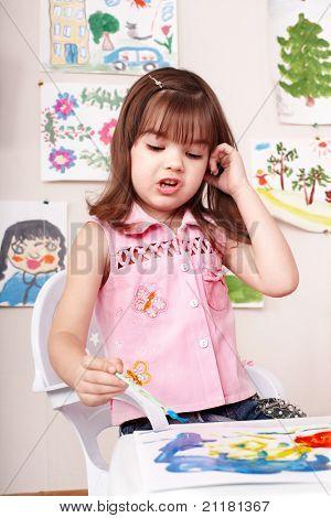 Little girl paint picture in preschool.