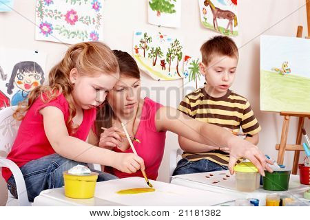 Children painting with teacher. Child development.
