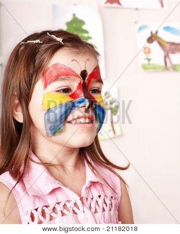 Little girl  making face painting.