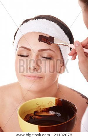 Girl having chocolate facial mask apply by beautician.
