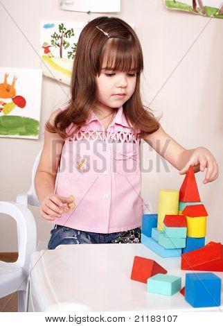 Niña jugando con bloque de madera en la habitación. Preescolar.