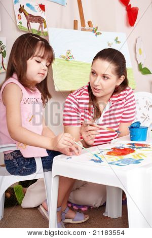 Little girl playing with teacher in preschool.