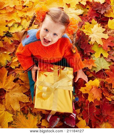 Little girl in autumn orange leaves and gift box. Outdoor.